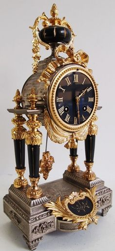 Antique Clock 19thc French 2 tone Gold & Silver Gilt Portico 8 day Mantle Clock - Rare design with polished black marble -It has gilt attachments with the most beautiful details and a rare design. Lovely tapered polished black marble pillars within cut gilt patterns allowing the pendulum to be clearly seen working in the open. It has ribbon decoration and hanging vines The pendulum has a protruding face mask It has a matching polished black marble dial with inset gilt numerals.