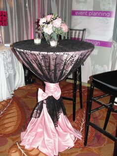 More final results bridal show table.  I think this was my favorite piece of the whole booth.  I got a bit of a funny look when I first suggested black lace for the cocktail table, but with the perfect shade of pink underlay and tie it turned out so great!  The florist captured exactly the right vintage glam  feel with this little cocktail table arrangement, and the silver mirrored cube vase they used was just a small touch that helped tie this table into the main table.