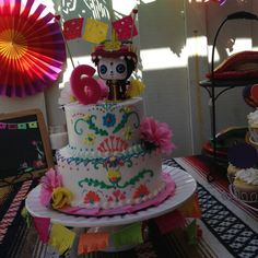Book of life birthday cake with La Muerte as a cake topper. Use Mexican embroidery theme to decorate the cake.