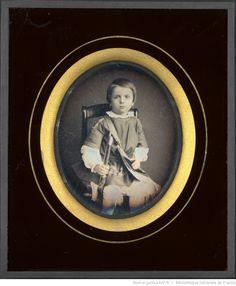 Portrait de petit garçon, à mi-jambes, assis, de trois-quarts à droite portant un fusil et une gibecière