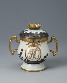 "Title:  Cream Bowl with a Lid  Complex: The Orlov Toilet Service with the Monogram ""GGO""  Place of creation: Russia, St Petersburg  Manufacture, workshop, firm:  Imperial Porcelain Factory  Authors: Project designer: 1738-1791; Painter:  Date: Second half of the 1760s  Material: porcelain, gold and silver  Technique:  underglaze cobalt painting, overglaze polychrome painting, gilding, silvering, selective polishing, chased  Dimensions:  a) 6х8,6х5,5 cm; b) 2,5х5,1 cm"