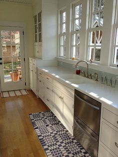 white kitchen cabinets, light blue/green backsplash, WINDOWS are amazing, even love the rugs!