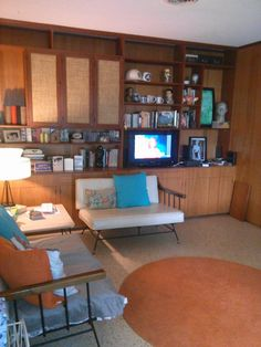 This is our living room #2 - our den. We adore the paneling and built-ins. Didn't change much! It also has the traditional Florida terrazzo floors. The furniture is a mid-century set - heavy duty with iron and wood framing.