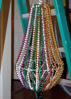 DIY: Mardi Gras bead chandelier. You can never have too many Mardi Gras beads as decor.  Cheap -- the beads are draped on a plant hanger -- and oh, so shiny! Mardi Gras Halloween Voodoo Masquerade Ball