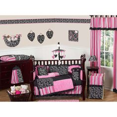 This black and pink themed 9-piece baby bedding set was created by Sweet Jojo Designs. This set includes a blanket, crib bumper, crib skirt, fitted sheet, toy bag, decorative throw pillow, diaper stacker, and two window valances.