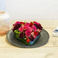 Zoek je iets speciaals? Deze verrassend rode bloementaart steelt echt de show. Rijk gevuld met rode rozen, paarse Tracheliums, Germini's en weer super hippe licht roze anjers. Leuk om te geven én om te krijgen!