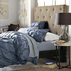 une tête de lit beige et tapissée dans la chambre à coucher aux accents bleus