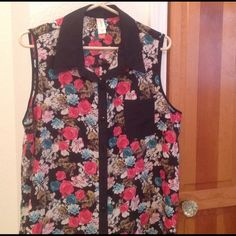 Sleeveless Blouse Very pretty sleeveless blouse, beautiful colors trimmed in black.  Longer back very flowing, worn once, you see I love buttons, my boobs make a nice opening for a peek-a-boo look.  100% polyester. No boundries Tops Blouses
