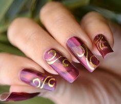 uñas largas decoradas con rojo y dorado