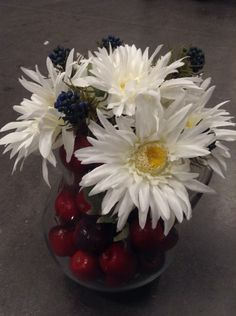 Patriotic style arrangement. Pitcher filled with mini apples and white daisies with some blue berries.