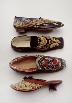 Albert slippers, England, 1860-80. Men's slippers, America, 1845-1855. Men's slippers, England, 1880-1895. Woman's mules, 1870-1880 © 2017 Bata Shoe M -- The lovely shoe at the top is an Albert slipper embroidered in black, blue, brown, and white wool. Below it, is a black velvet house slipper with colourful paisley needlework. The next slipper is embroidered with roses in Berlin wool work and like the other two above it, it is a men's shoe meant to be worn within the home. Last, ...