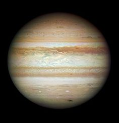 Giant Jupiter. The dark smudge at bottom right is debris from a comet or asteroid that plunged into Jupiter's atmosphere and disintegrated. In addition to the fresh impact, the image reveals a spectacular variety of shapes in the swirling atmosphere of Jupiter. The planet is wrapped in bands of yellow, brown and white clouds. These bands are produced by the atmosphere flowing in different directions at various places. When these opposing flows interact, turbulence appears.
