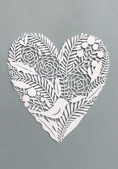 A lovely and intricate heart shaped cut out with more details inside. You can see flowers, ferns and leaves adorning the rather plain and white entirety of the shape.