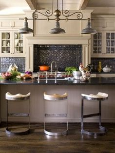 Exposed wooden ceiling beams, slatelike granite countertops, and industrial-style stools with butcher-block seats create charm in the English country-style kitchen. The expansive island provides plenty of space to cook and gather. (Photo: Emily Minton Red