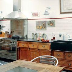 Une cuisine avec des éléments classiques en accord avec l'esprit du lieu.   les meubles moulurés de sa cuisine. Réalisés sur mesure par un menuisier,  sont en chêne massif ciré avec du Baume des Antiquaires (coloris chêne moyen). Le timbre d'office en pierre bleue du Hainaut a également été fait sur mesure. À ce décor classique, il a mélangé quelques éléments modernes: une cuisinière de pro  et une crédence en inox qui protège le carrelage d'origine surmonté d'un listel rouge.