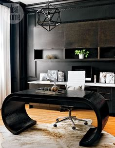Dark and dramatic—The rich black walls offer a moody, masculine look and also camouflage the dark cabinetry. While the moulding gives the office added character, intriguing elements like the vintage Karl Springer-like waterfall desk and the geometric pendant light create a dramatic setting.