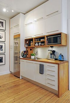 Love the cupboards, the organization of the shelving, the black & white photos, and the wooden floors. A colorful rug would pull this all together.