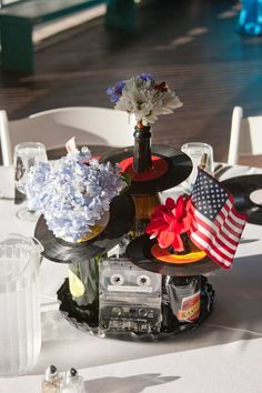 Vinyl record, Cassette tape and Themed Beer Bottle Centerpiece: switch out the flowers for sunflowers, red roses, and tiger lillies. instead of the flag sticking out, put the table number.