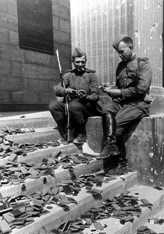 Smoke break at the steps of the Reich Chancellery, May 1945. At the feet of the smokers hundreds of decoration cases. They are of no use any longer.