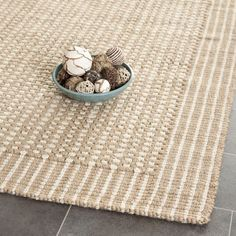 An elegant contemporary loop design and a jute pile highlight this handmade rug. This rug has a beige background and displays stunning panel colors of beige and ivory.