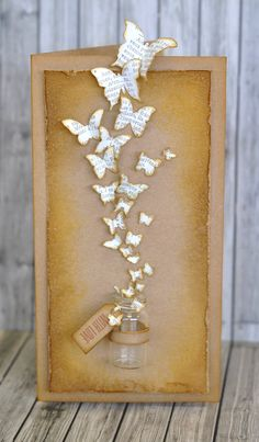 handmade card ... tall and thin format ... kraft card and main panel aged with sponged ink and roughed up edges ...swarm of butterflies punched from book paper ... luv it!