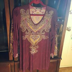 Tunic Very pretty and comfy tunic.  Feels great on,  doesn't wrinkle,  can be machine washed and dried.  Looks great with jeggings, jeans,  capris or a skirt.   Has wine,  gold, pale pink and brown colors.   Goes with so much.   Full flowy sleeves with pleats.   Design front and back and on sleeves.   In excellent condition, will last for years. Citiknits Tops Tunics