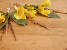 Vintage Gathering Wedding Flowers: Buttonholes for a summer wedding created from wild grasses, yellow Freesia and some greenery.
