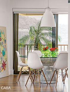 Na mesa de jantar, assinada por Warren Platner (1919-2006), os vasos de vidro (LZ Studio) espalham seu colorido. Cadeiras da Tok & Stok e tela apoiada no piso de Gláucia Leme.
