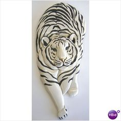 wall-hung wood carving of white tiger stalking