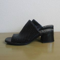 Black on black leather sandals with a woven upper and chunky block heel. Perfect with pants or skirts. These minimal slip-ons are open toe