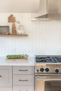 neutral farmhouse kitchen design with white herringbone tile and gray kitchen cabinets