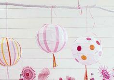 Streifen, Kreise oder andere Motive nach Wahl aus farbigem Transparentpapier ausschneiden.    Bastelkleber dünn auf das Transparentpapier auftragen und die Motive fest auf den Lampenschirm drücken. An den unteren Metallstreben der Ballonlampen kann man zusätzlich schöne Bänder festbinden, die im Wind wehen.    Zur reinen Deko werden die Ballonlampen, wenn man Sie mit Bändern an der Zimmerdecke, am Sonnenschirm oder am Balkon befestigt.