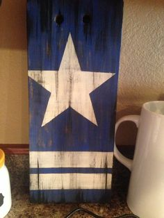Dallas cowboys sign. Old scrap wood painted blue, added vintage dallas star. Painted over with black.