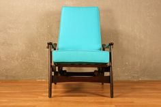 Sleek danish modern rocking lounge chair with vibrant cerulean blue cushions. A firm and comfortable seat featuring curved armrests. In overall good condition with minor nicks to the frame. Dimensions: 29w 25.5d 39h