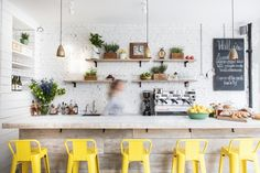 Hally's Parsons Green, limed wood bar with  white Carrara marble top and yellow Tolix chairs | Remodelista