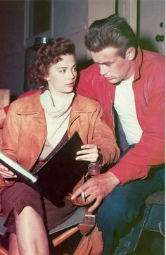 "Natalie Wood and James Dean reading during a break in the filming of Rebel Without a Cause (1955). RWAC is a violent, brutal and disturbing picture of modern teenagers. Mr. Dean is a mixed-up rebel because his father lacks decisiveness and strength. ""If he only had the guts to knock Mom cold once!"" Mr. Dean mumbles longingly. And Miss Wood is wild and sadistic, prone to run with surly juveniles because her worrisome father stopped kissing her when she was 16."