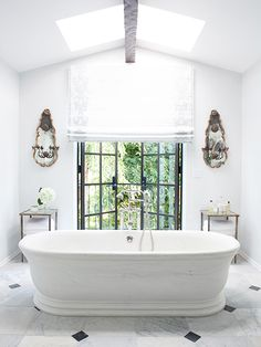 The Best Bright White Spaces//marble bathtub, mirrored sconces, skylight, french doors