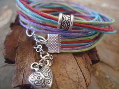 This bracelet consists of 8 handmade cotton belts in great colors of lilac, turquoise, red and grass green, which were provided with a great spacer.