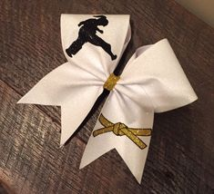Taekwondo/Karate full glitter bow with belt. Made to order, you pick the color of the belt. **Please leave color choice for belt in the notes to seller section.**   Each bow is made with 3 inch ribbon and measures approx. 6-7 inches wide. This order will ship as shown. If you would like the changes the colors please leave a detailed not in the notes to sellers section upon ordering. **All designs are personally designed by me. You will be getting one of a kind Designs. Please note that ...