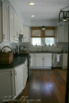 White cabinets (Benjamin Moore Moonshine), marble tile backsplash (Venatino Polished Marble), honed finish granite countertops (Virginia Jet Mist), zero radius sink, Bamboo Floors (Cali Bamboo,Antique Distressed Java)