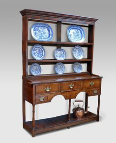 Now in - Small charming eighteenth century oak dresser with lovely golden colour. Moulded cornice over the rack of three shelves with lipped plate supports. The base section with three beaded drawers fitted with brass plate handles. Shaped apron flanked by two dummy drawers. Potboard below with turned supports and raised on block feet. circa. 1750