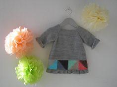 Vestido simétrico en mezcla de punto bobo y punto del revés que puede llevarse por los dos lados. En uno, lleva dos botones de madera en el cuello y los colores de la cenefa de triángulos del volante, son distintos en cada lado.   Colores:  28-1  GRIS PLATA    Tallas:  3-6 meses (56-68 cm) 6-9 meses (68-74 cm) 9-12 meses (74-80 cm) 1-2 años (80-92 cm)