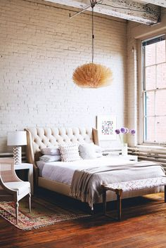Look We Love: Luxe Industrial via @domainehome  High ceilings and exposed pipes and beams feel surprisingly cozy thanks to this bedroom's luxurious tufted bed, styled with a variety of textures and fabrics.