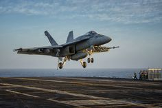 """A Boeing F/A-18E Super Hornet, from Strike Fighter Squadron 14 (VFA-14) """"Tophatters,"""" returning to the USS John C. Stennis (CVN 74)."""