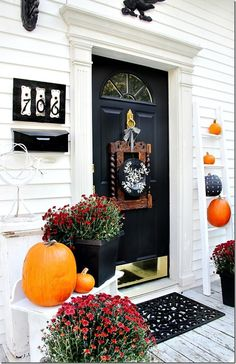 Back door decorated for fall with an old chair back on the door, chalkboard pumpkins and vintage house numbers.  thistlewoodfarms.com