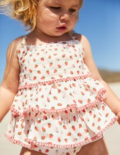 There are lots of things that make this playsuit sweet – and we're not even talking about the strawberry print. Made of lightweight cotton, it has pretty ruffles and pompom details, with extendable shoulder straps and poppers at the bottom to make dressing baby a doddle.