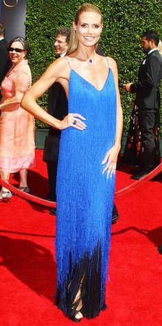 Project Runway host Heidi Klum stole the spotlight at the 2014 Creative Arts Emmy Awards in a custom blue fringed creation by Project Runway contestant Sean Kelly, which swished with her every step. She color-coordinated her look with Lorraine Schwartz sapphire jewelry.