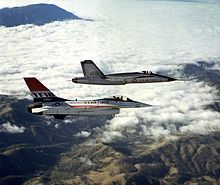 Two jet aircraft flying together over mountain range and cloud.