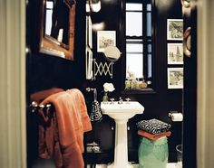 I'm planning on painting my powder room a dark color to eliminate the beige box and add a hint of drama to the otherwise boring bathroom.