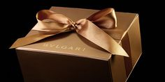 Bulgari Metallic gold rigid collapsible box with foil stamped logo, ribbon tie, and front flap magnetic closure.